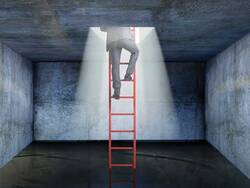 man climbing ladder out of darkness