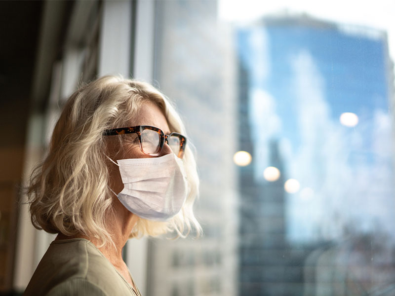 Mature businesswoman looking out of window with face mask