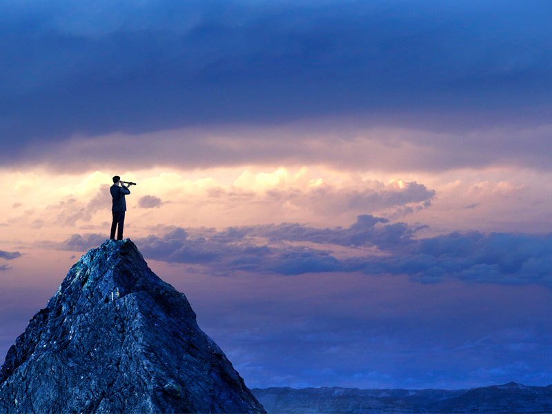 A silhouetted businessman stands on top of a mountain peak and looks into the distance with a spyglass in front of a dramatic sunset in the distance