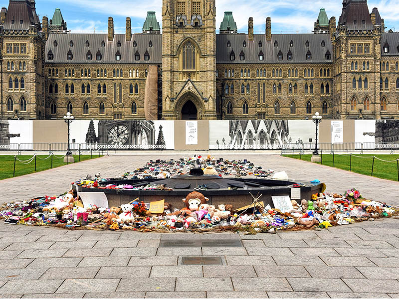 Ottawa, Canada - June 30, 2021: The many shoes and toys left near the Centennial Flame on Parliament Hill in memory of the children whose remains were found near former Residential Schools.