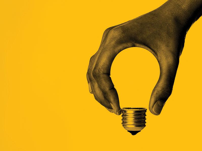Hand holding a light bulb